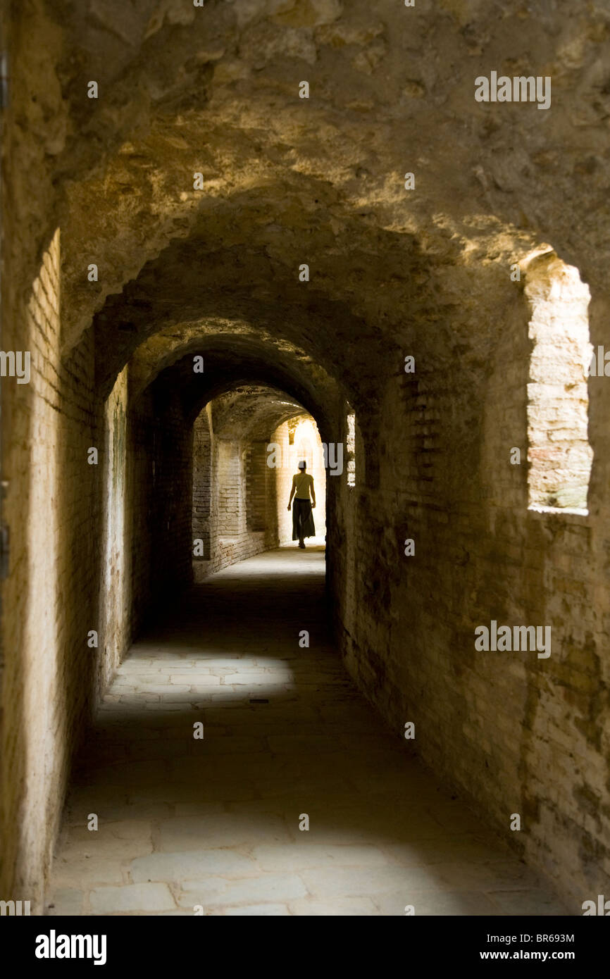 Distant tourist in hallway that circles the amphitheatre at the ruined Roman city of Italica / Itálica near Seville, Stock Photo