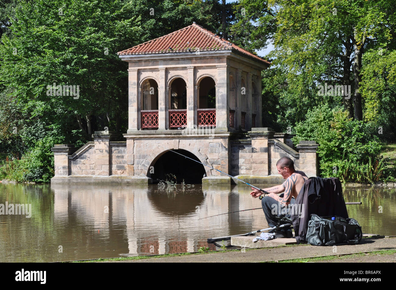 Fishing close to The Boathouse in Birkenhead Park - Stock Image