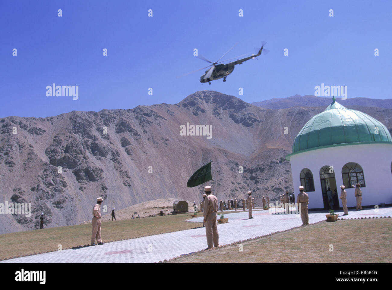 Guards stand at attention as helicopters fly in salute over the shrine of Ahmad Shah Masood in the Panjshir Valley - Stock Image