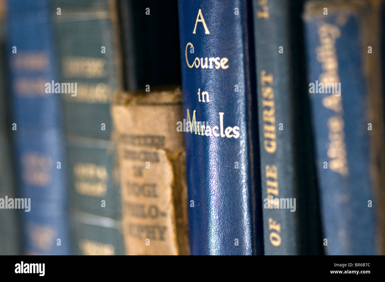 Esoteric,Religious books in bookshelf with focus on A Course in Miracles - Stock Image