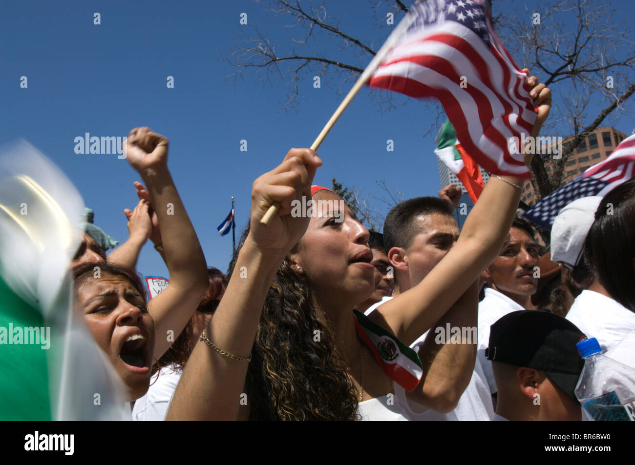 Demonstrators wave American flags and chant at a May Day rally for immigrant rights in Denver Colorado - Stock Image