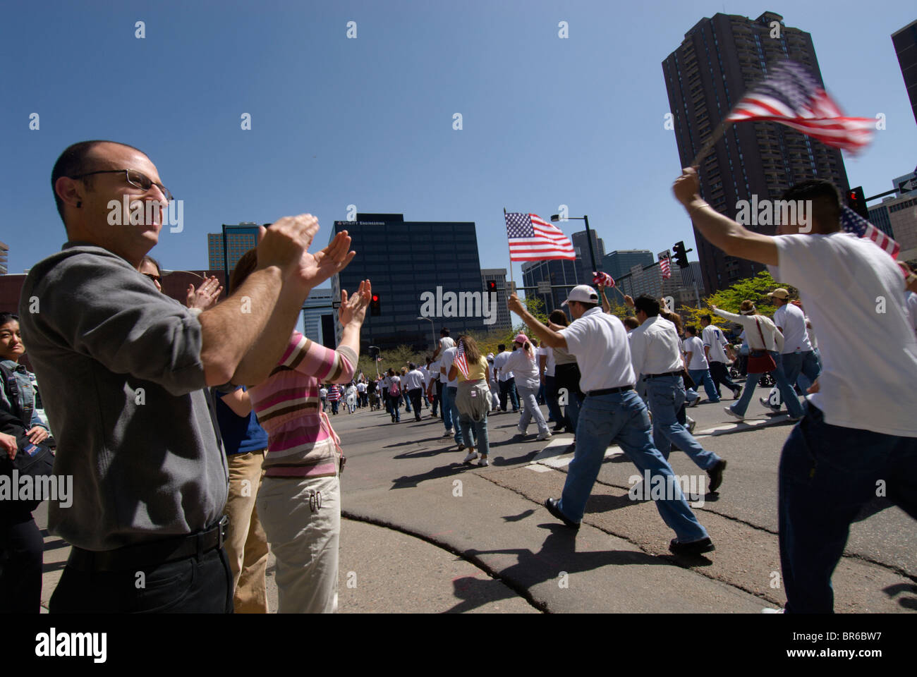 Downtown office workers applaud Latino demonstrators as they march for immigrant rights in Denver Colorado - Stock Image