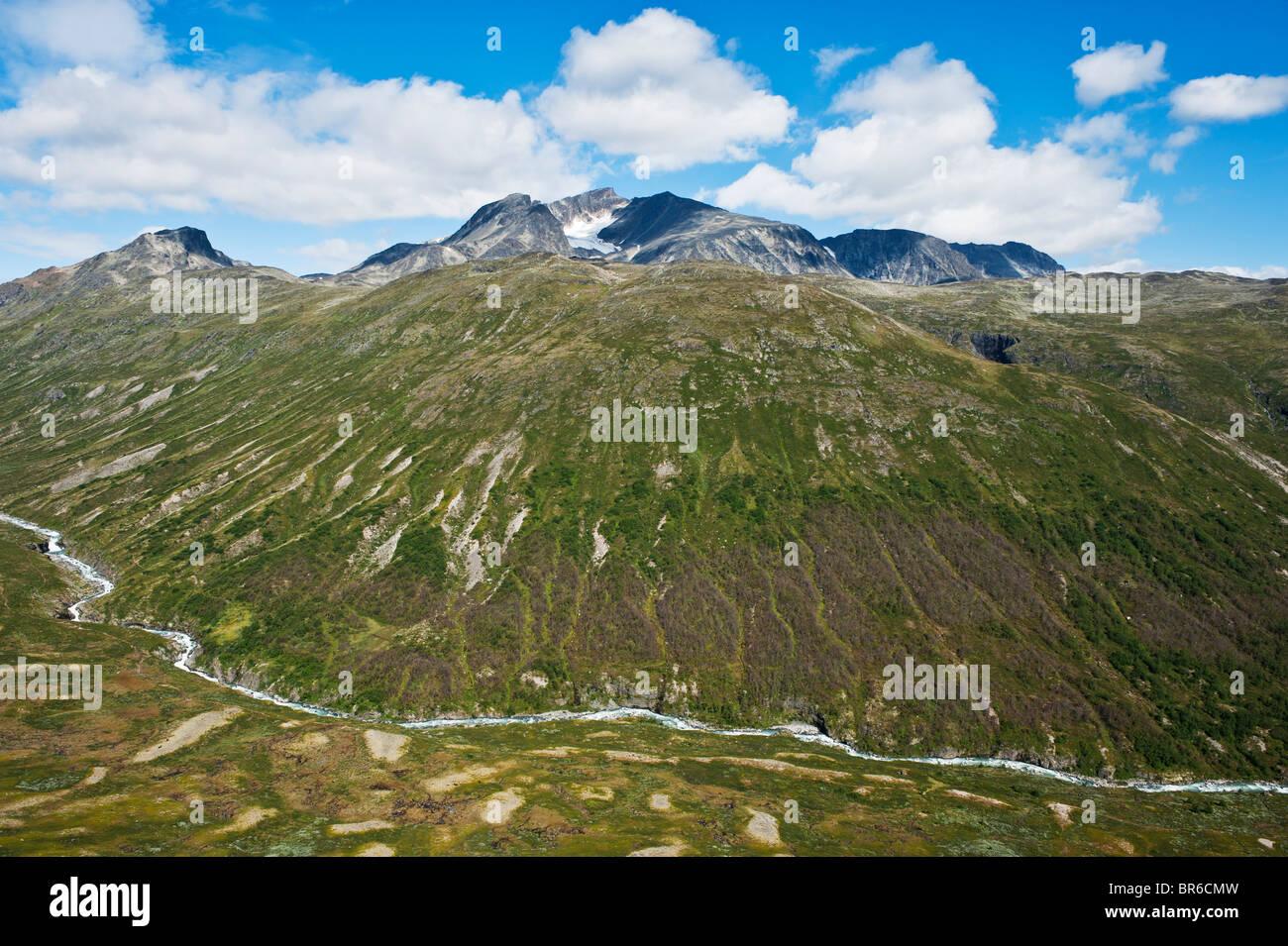 Surtningssue mountain peak rises above Memurudalen river valley, Jotunheimen national park, Norway - Stock Image