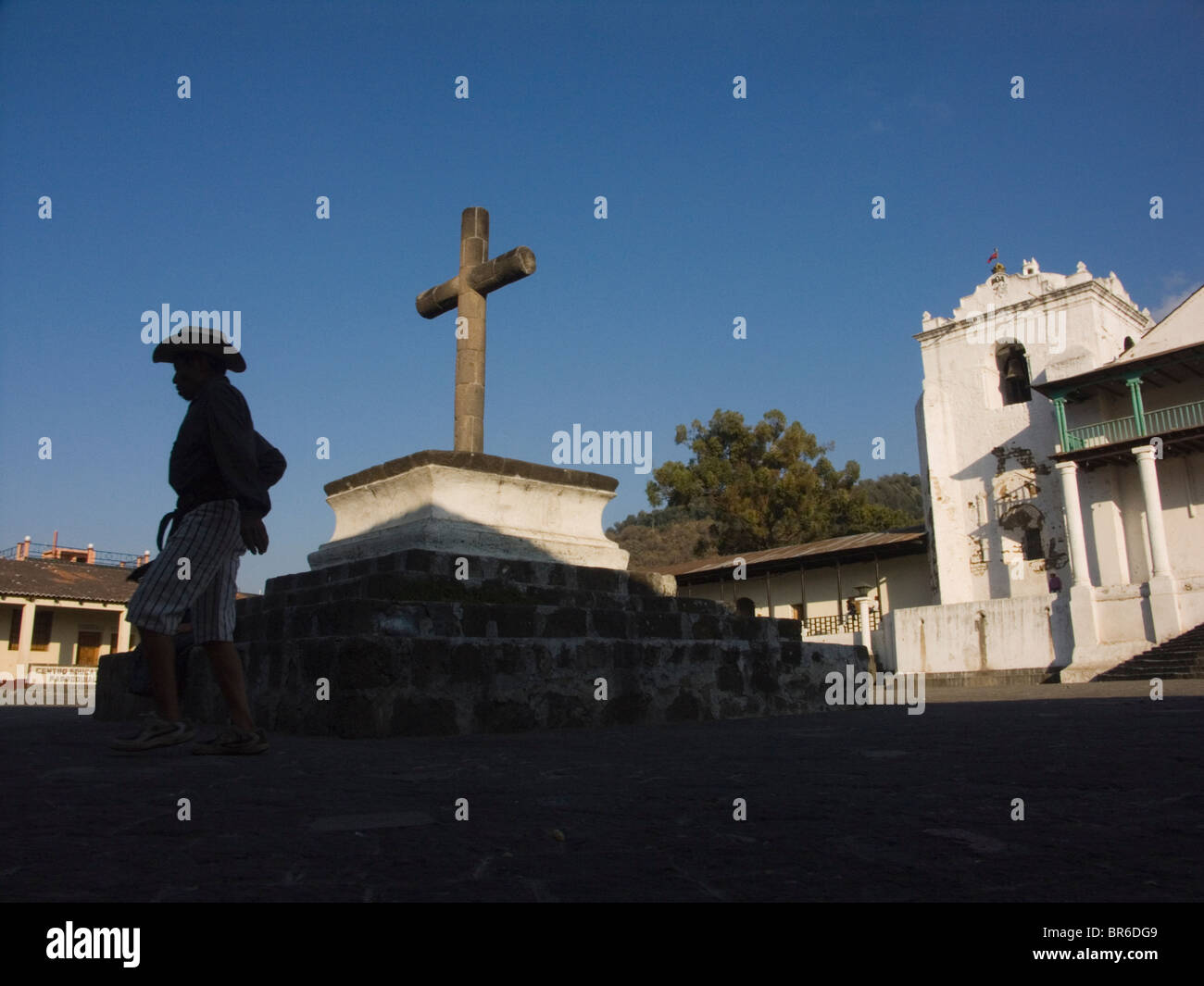 A man silhouetted walks in front of a church. Santiago Guatemala. - Stock Image