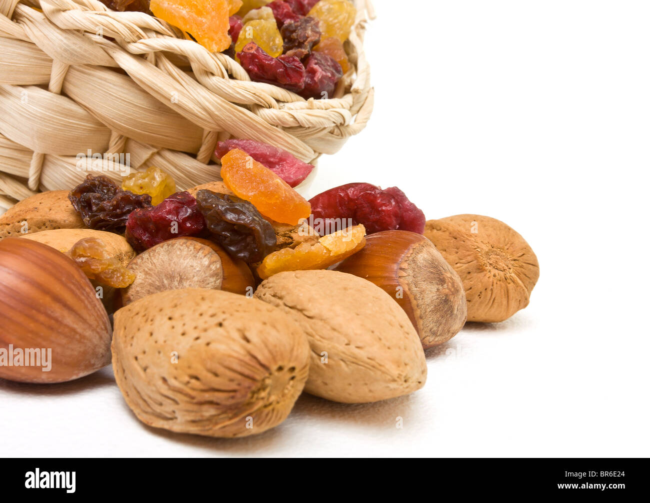 Mixed dried fruits and nuts spilling from basket on white background. - Stock Image