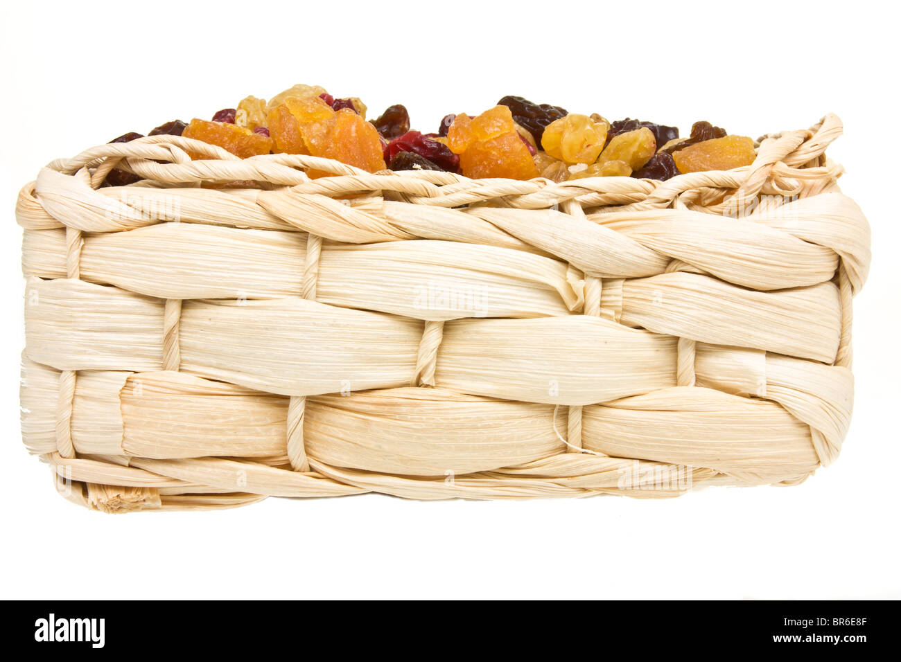 Mixed Dried Fruits of Apricots, sultana, raisins and cranberries in wicker basket. - Stock Image