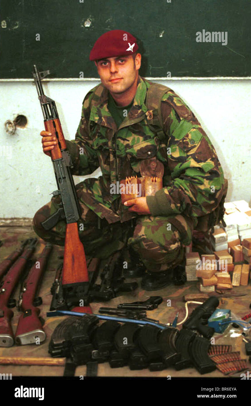 A British Paratrooper pose with captured  weapons in Pristina, Kosovo. Stock Photo