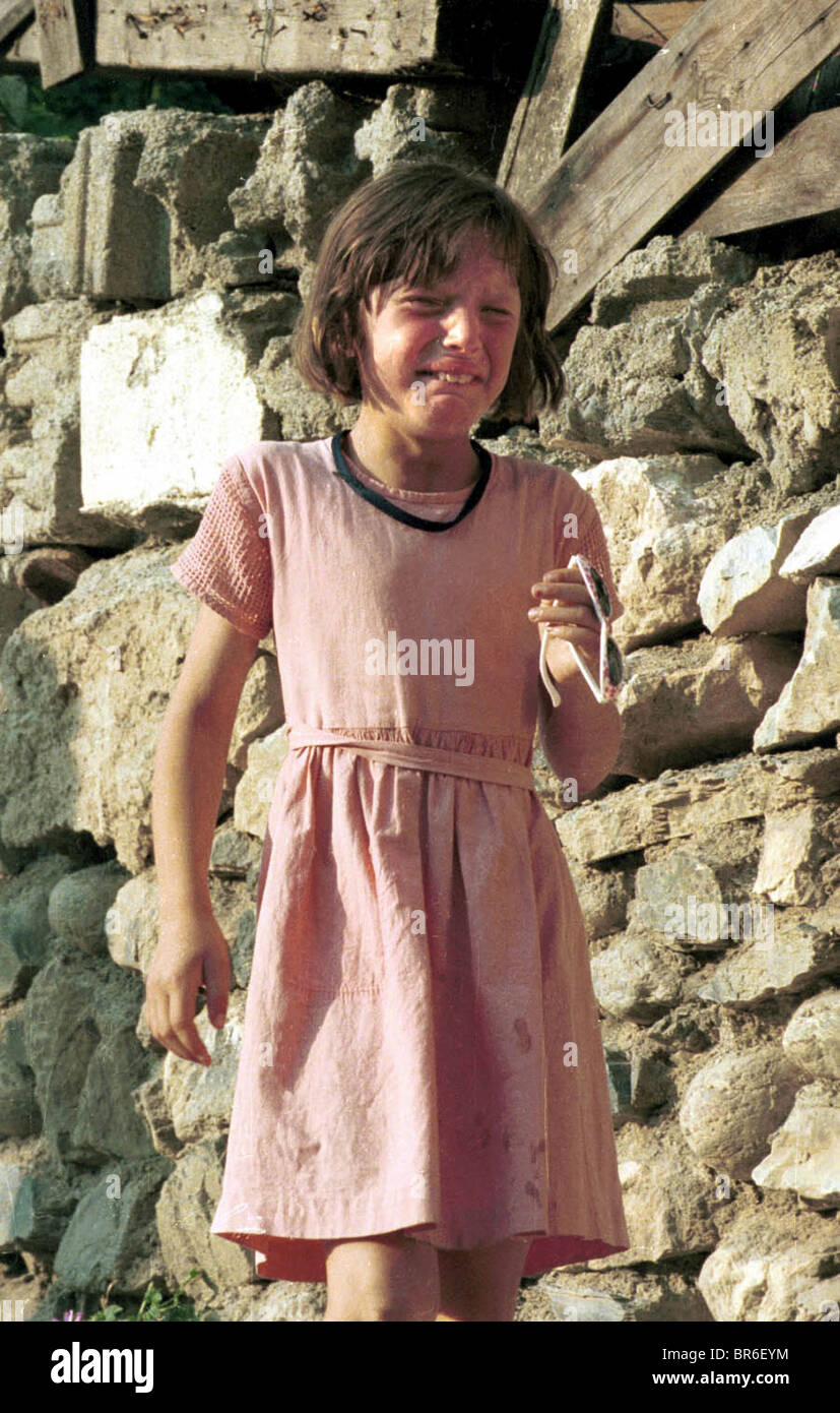 A child reacts to her home being burned down in Prizren, Kosovo. Stock Photo