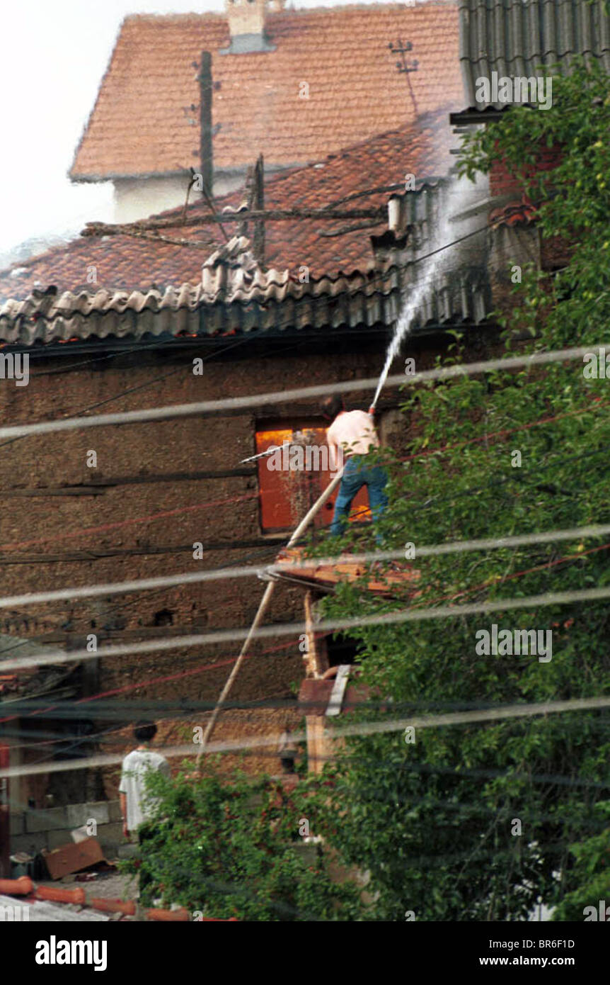 Men put out home fires allegedly set by Albanians who wanted to burn Serb homes in Prizren, Kosovo. Stock Photo