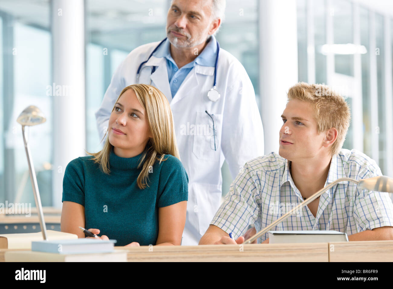 Medical students with professor in classroom studying - Stock Image