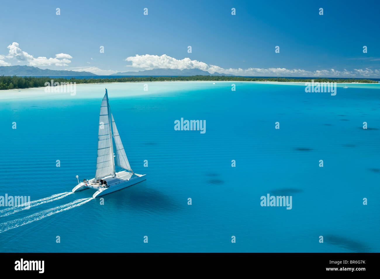 Catamaran sailing boat in the clear blue water lagoon of Bora Bora - Stock Image