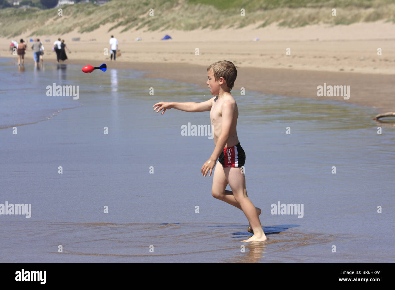Boy standing in shallow water and throwing a nerf ball on a beach in Woolacombe North Devon UK Stock Photo