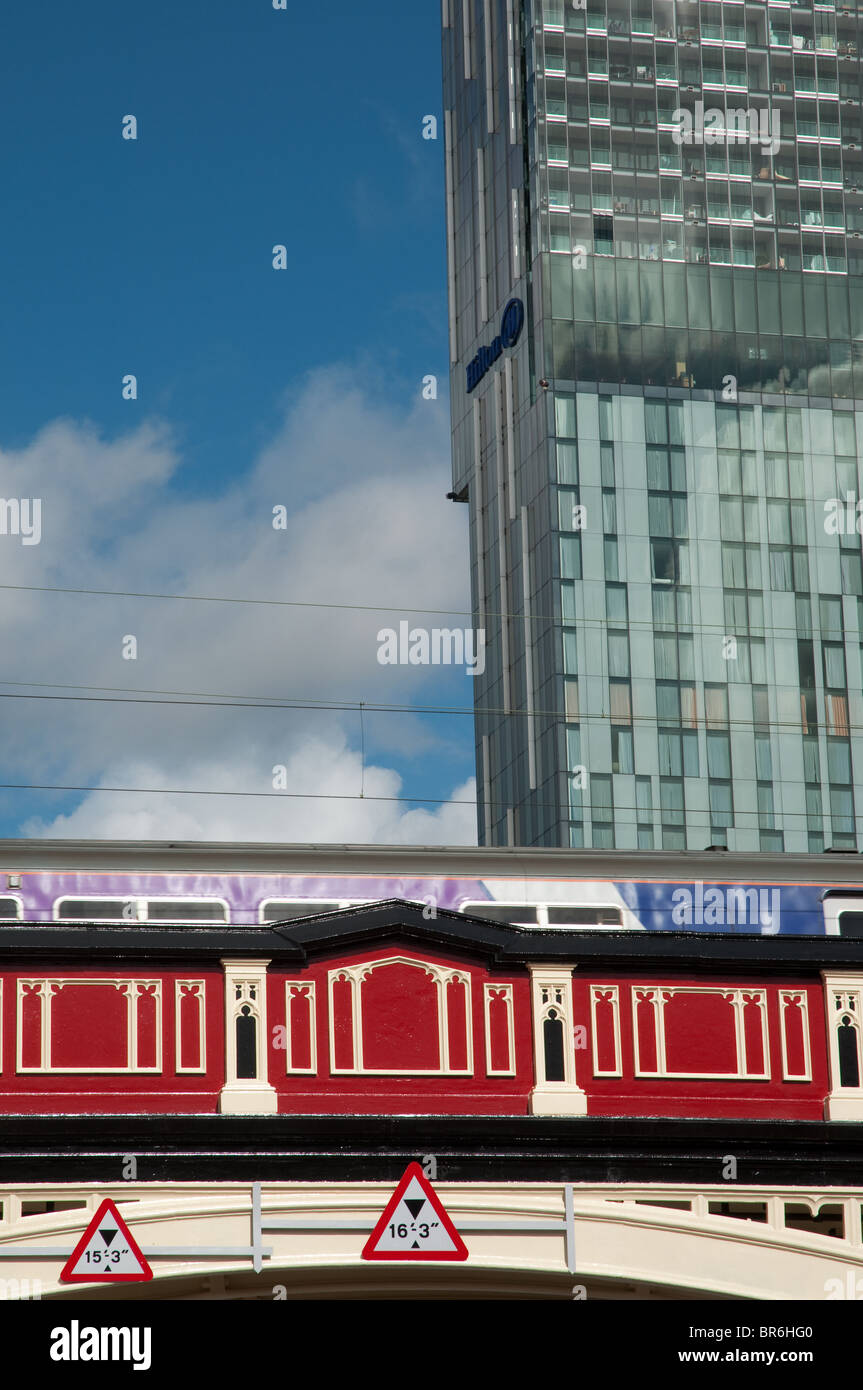 Train traveling over bridge.Deansgate central Manchester.Beetham Tower/Hilton Hotel in the background. - Stock Image