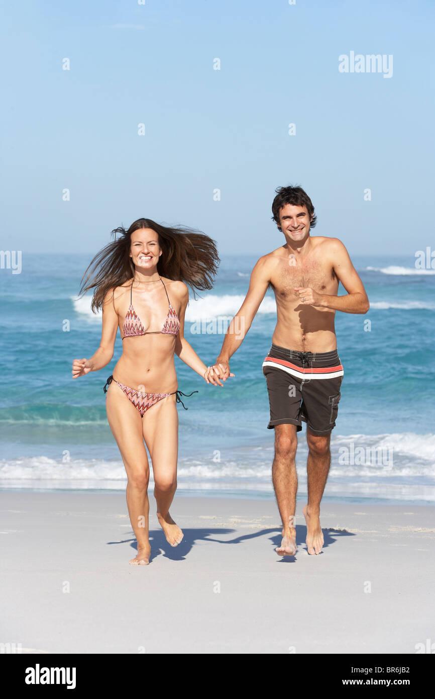 Young Couple Running On Beach Wearing Swimwear Stock Photo