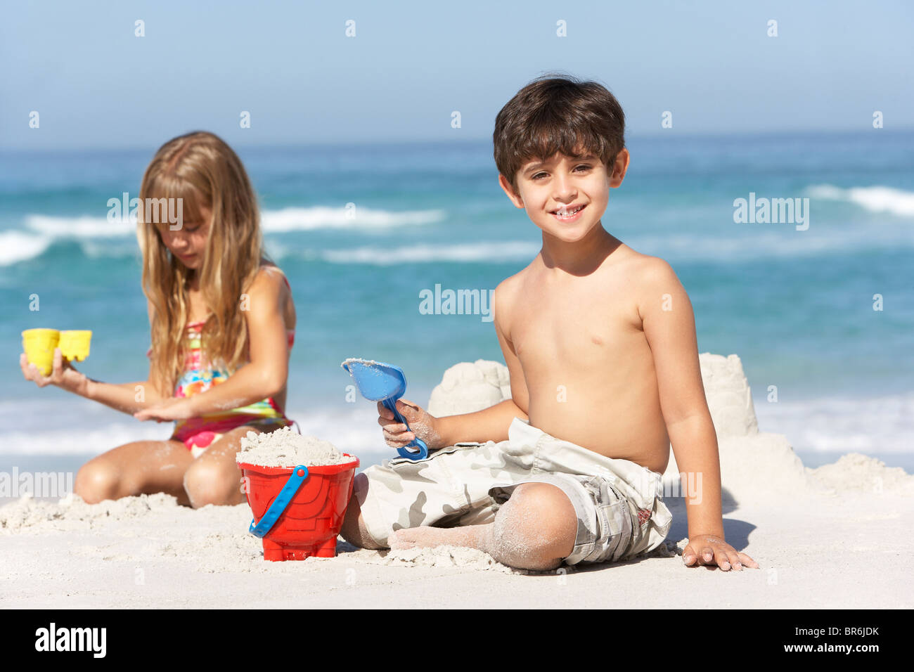 Children Building Sandcastles On Beach Holiday - Stock Image