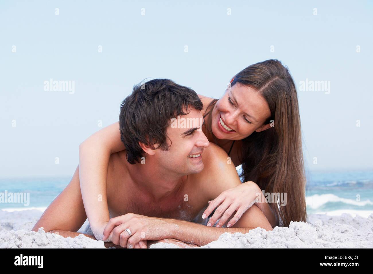 Young Couple Relaxing On Beach Wearing Swimwear - Stock Image