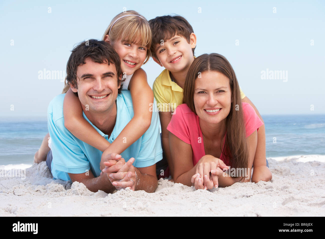 Family Relaxing On Beach Holiday - Stock Image