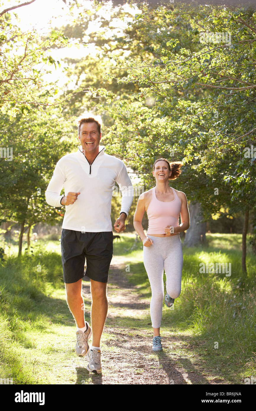 Middle Aged Couple Jogging In Park - Stock Image