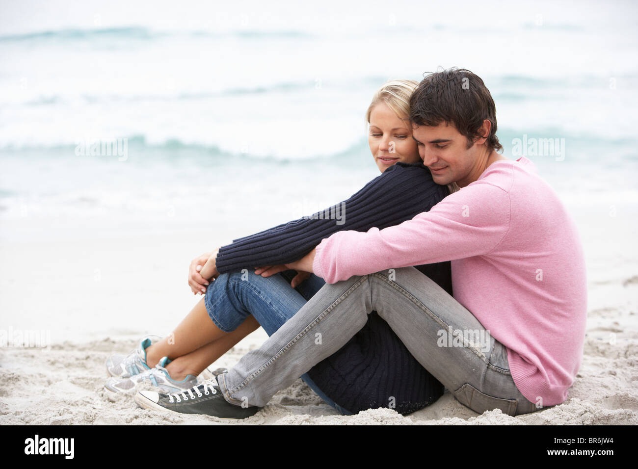 Young Couple On Holiday Sitting On Winter Beach - Stock Image