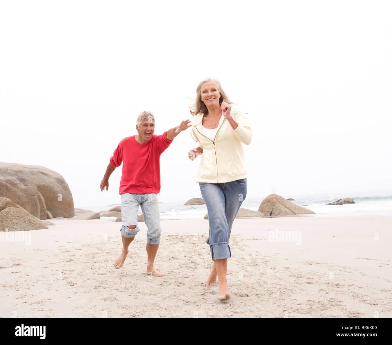 Senior Couple On Holiday Running Along Winter Beach - Stock Image