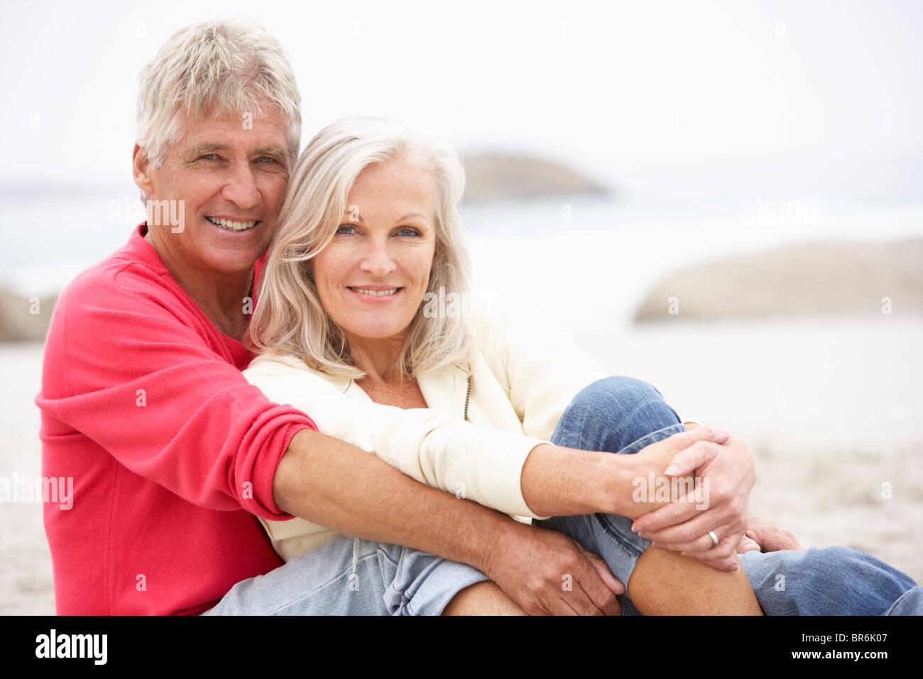 Senior Couple On Holiday Sitting On Winter Beach - Stock Image