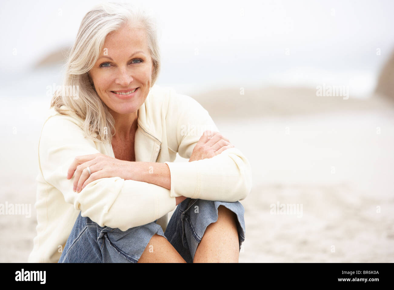 Senior Woman On Holiday Sitting On Winter Beach - Stock Image