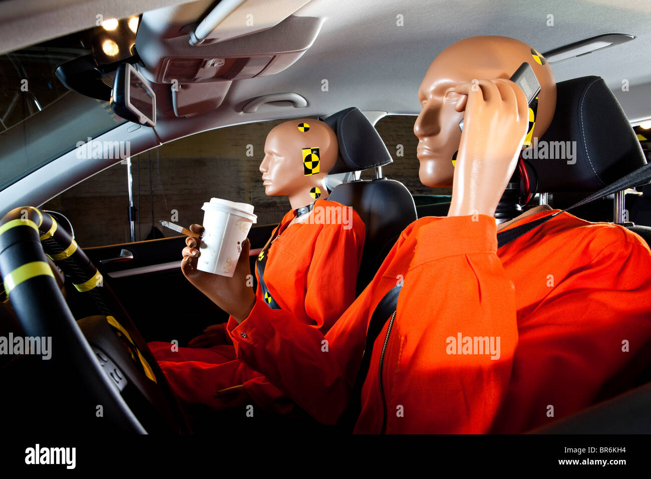 A crash test dummy carelessly using a mobile phone while driving with a crash test dummy passenger - Stock Image