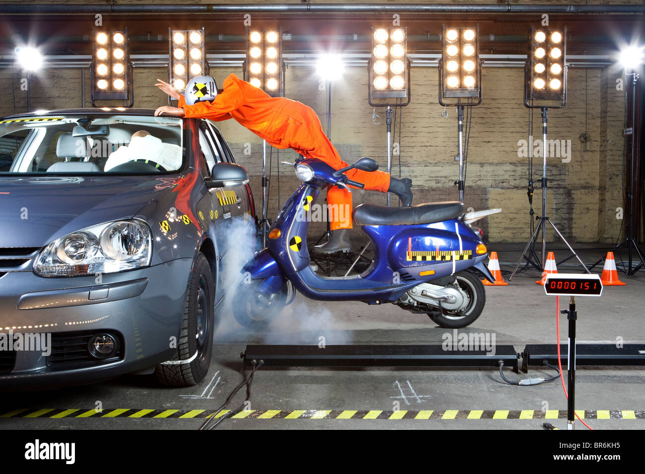 A crash test dummy on a scooter crashing into a car Stock
