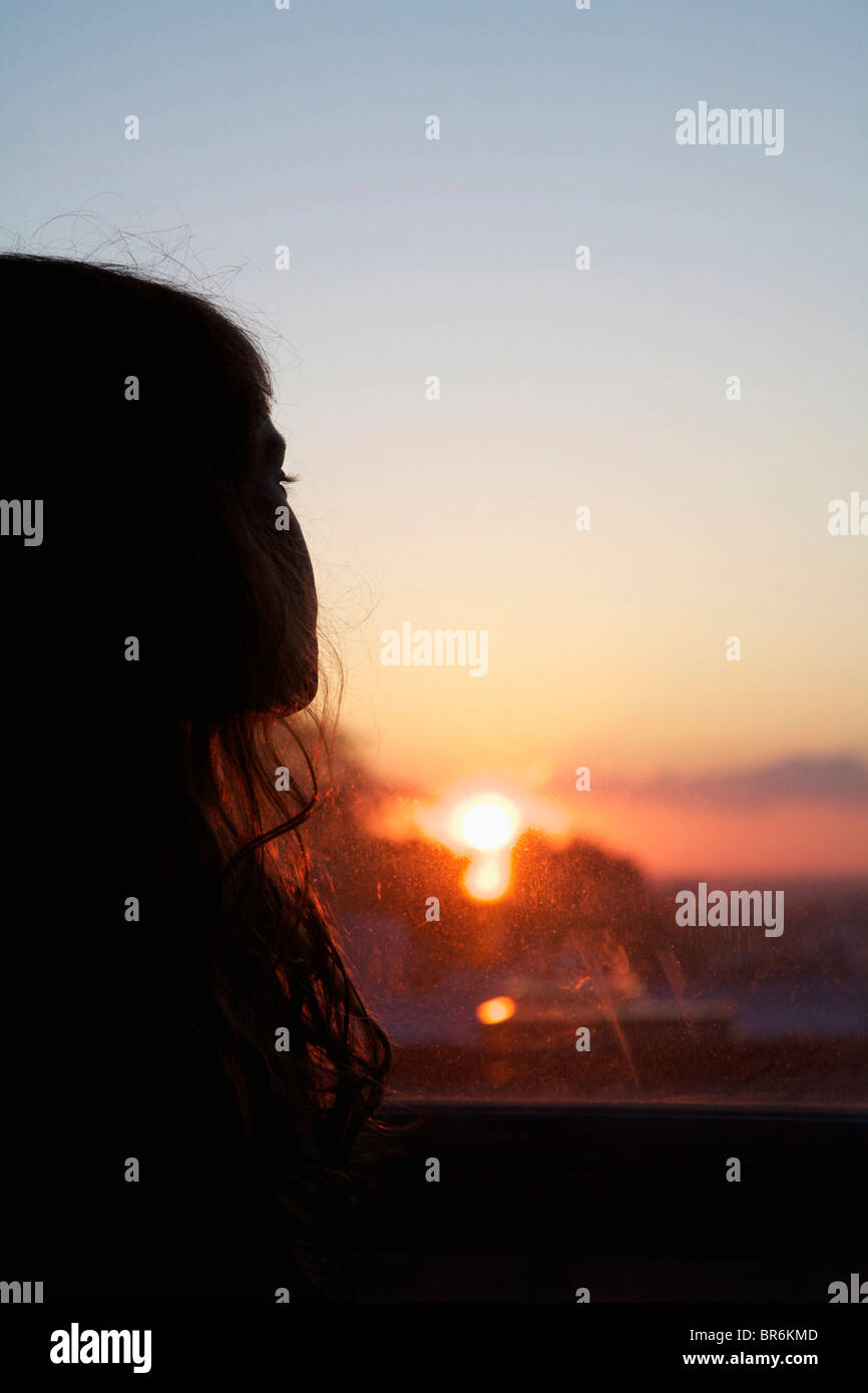 A girl looking out a window at sunset - Stock Image