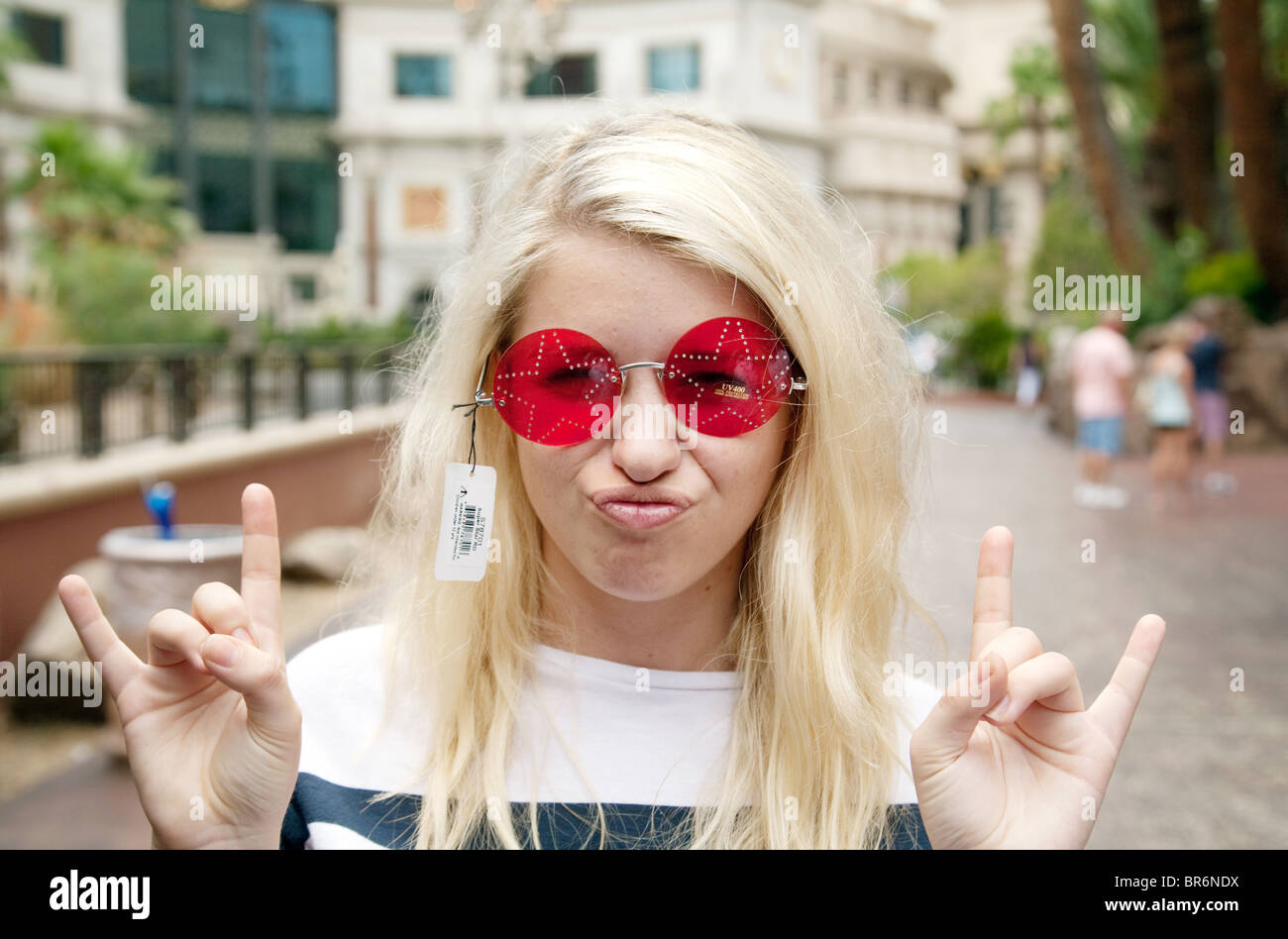 A blond teenage girl trying on a pair of rose tinted glasses, the Strip, Las Vegas USA - Stock Image