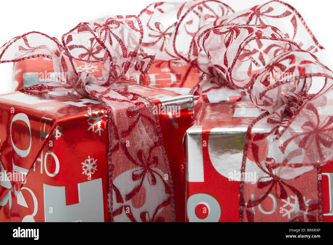 Pretty wrapped Christmas presents in red and silver foil with fancy red ribbon Stock Photo
