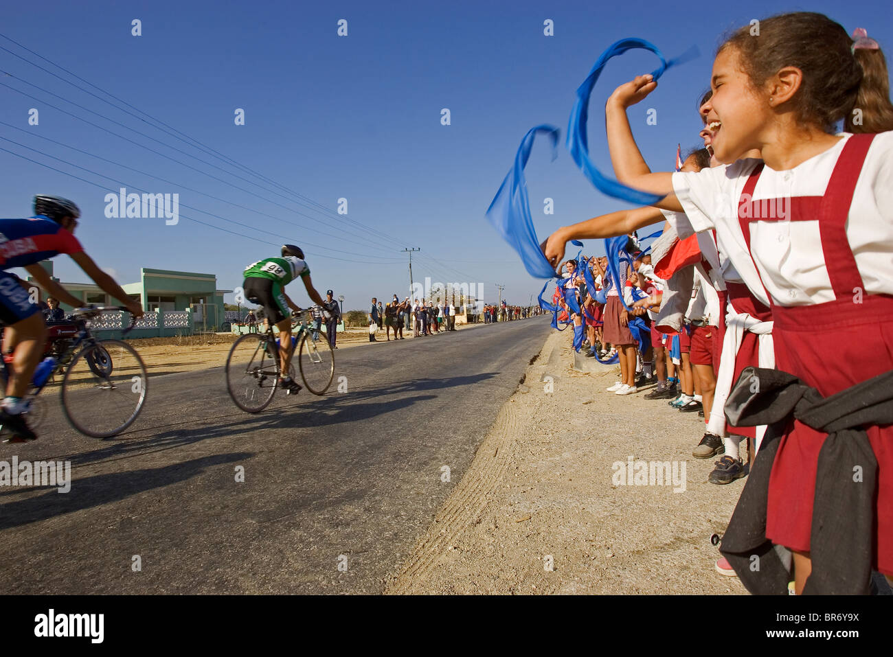 Children wave handkerchiefs at cyclers as they go past in the street in Cuba. - Stock Image