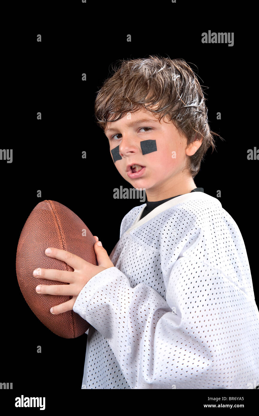 A young, sweaty quarterback football player holds his football and gives an attitude. - Stock Image