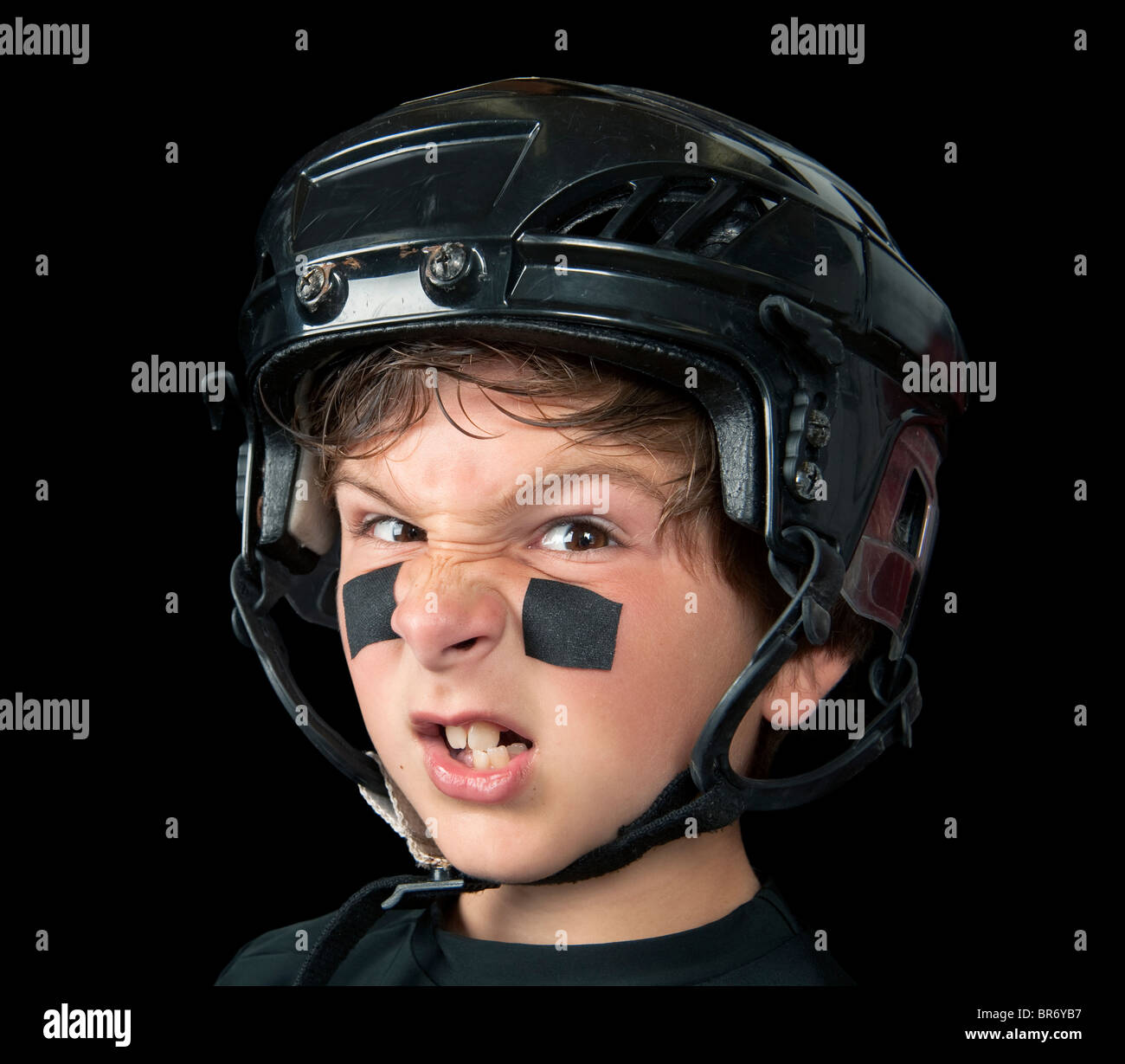 A youth hockey player wearing protective headware snarls at the camera - Stock Image