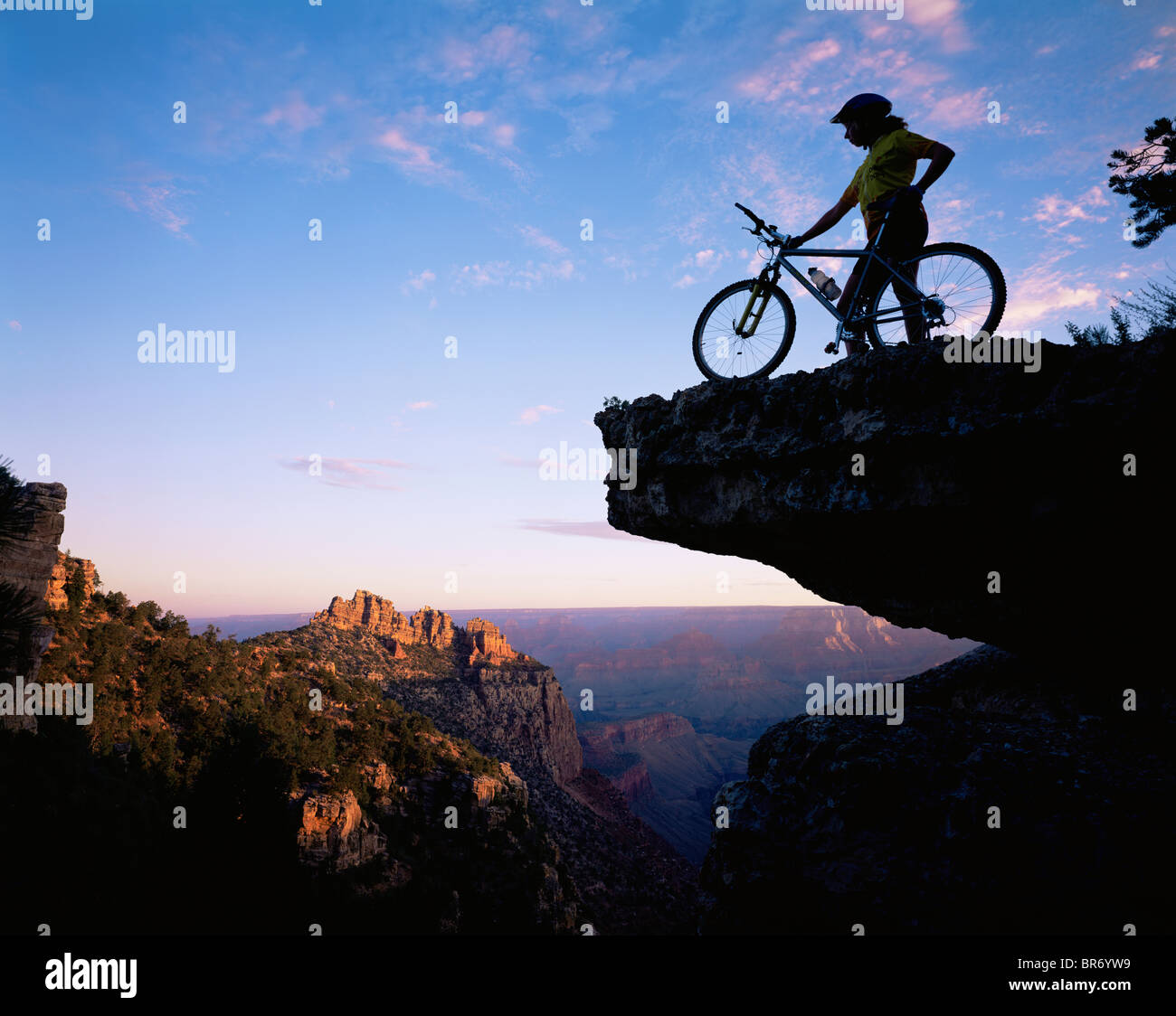 Mountain Biker stood on a ridge at sunrise overlooking the Grand Canyon, Grand Canyon NP, Arizona, USA - Stock Image