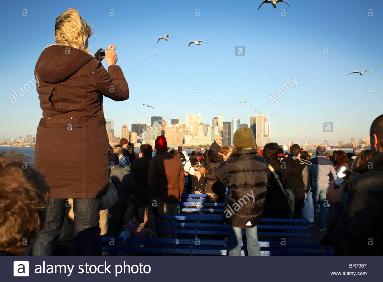 Tourists get a view of NYC from the Ellis Island ferry. - Stock Image