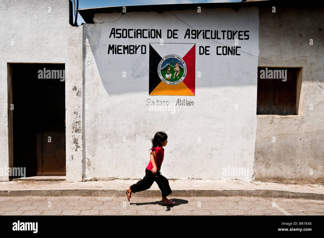 A child running in front the CONIC NGO bureau, San Juan la Laguna, Solola, Guatemala. - Stock Image