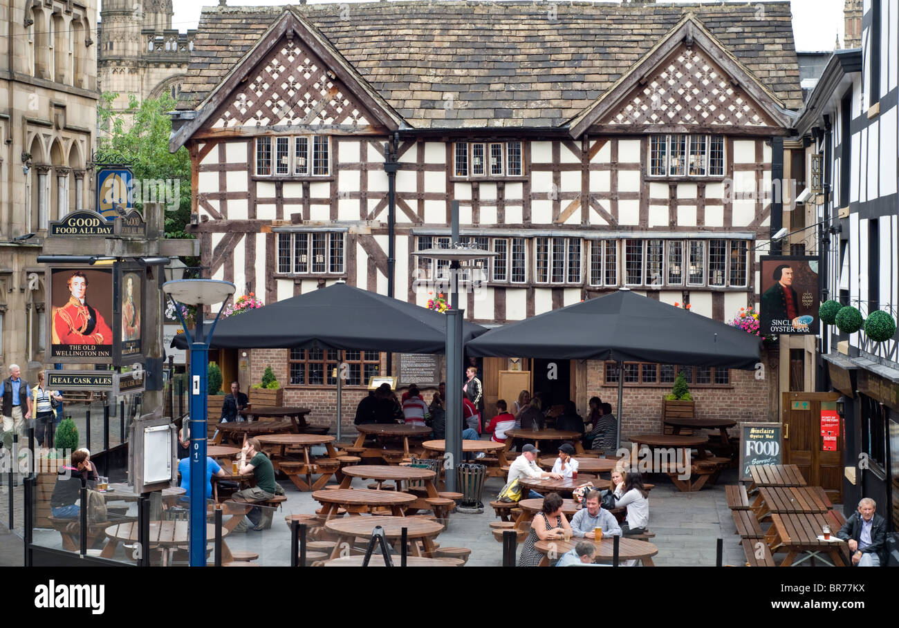 People drinking outside the Old Wellington Inn in Manchester city centre, England, UK - Stock Image