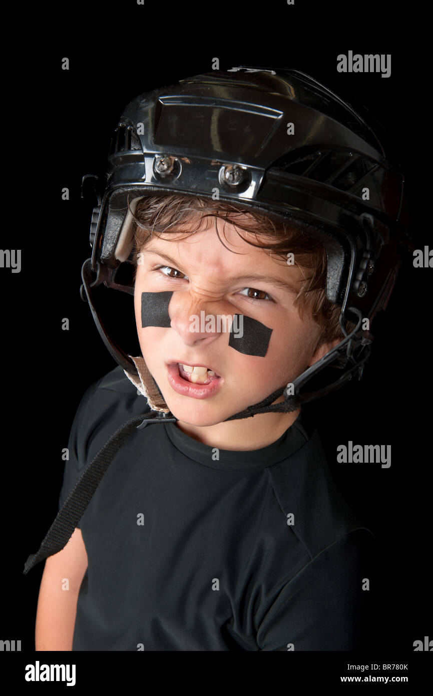 A sweaty youth hockey player wearing his safety helmet snarls at the camera. - Stock Image
