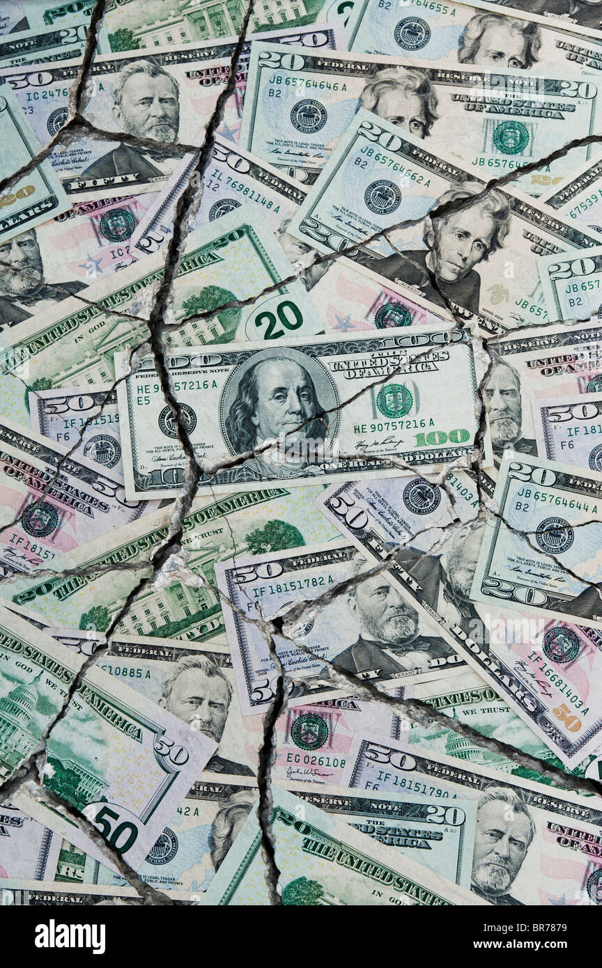 Cracked  American dollar bills concept to represent an economic crisis - Stock Image