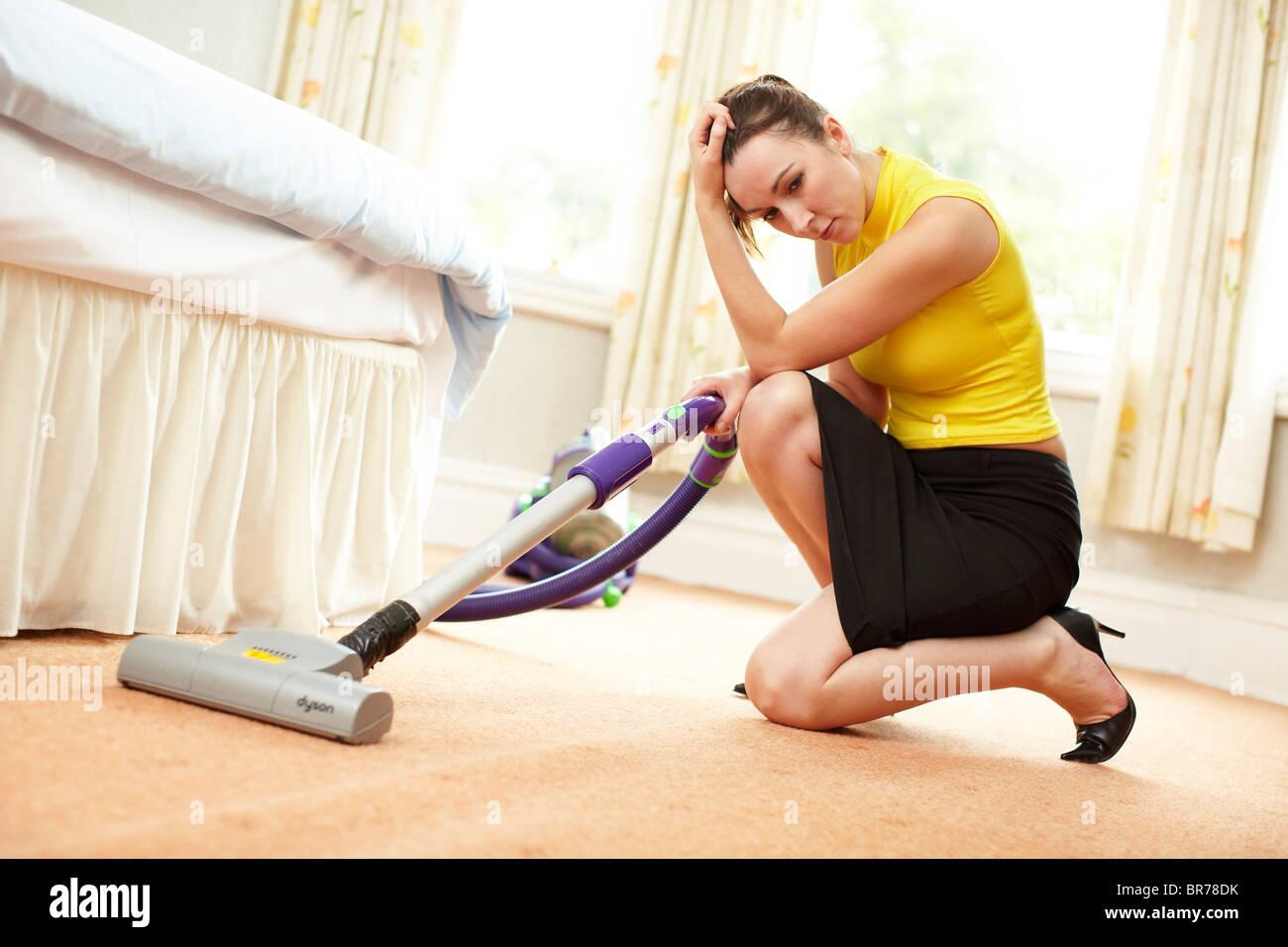 Woman using vacuum cleaner - Stock Image
