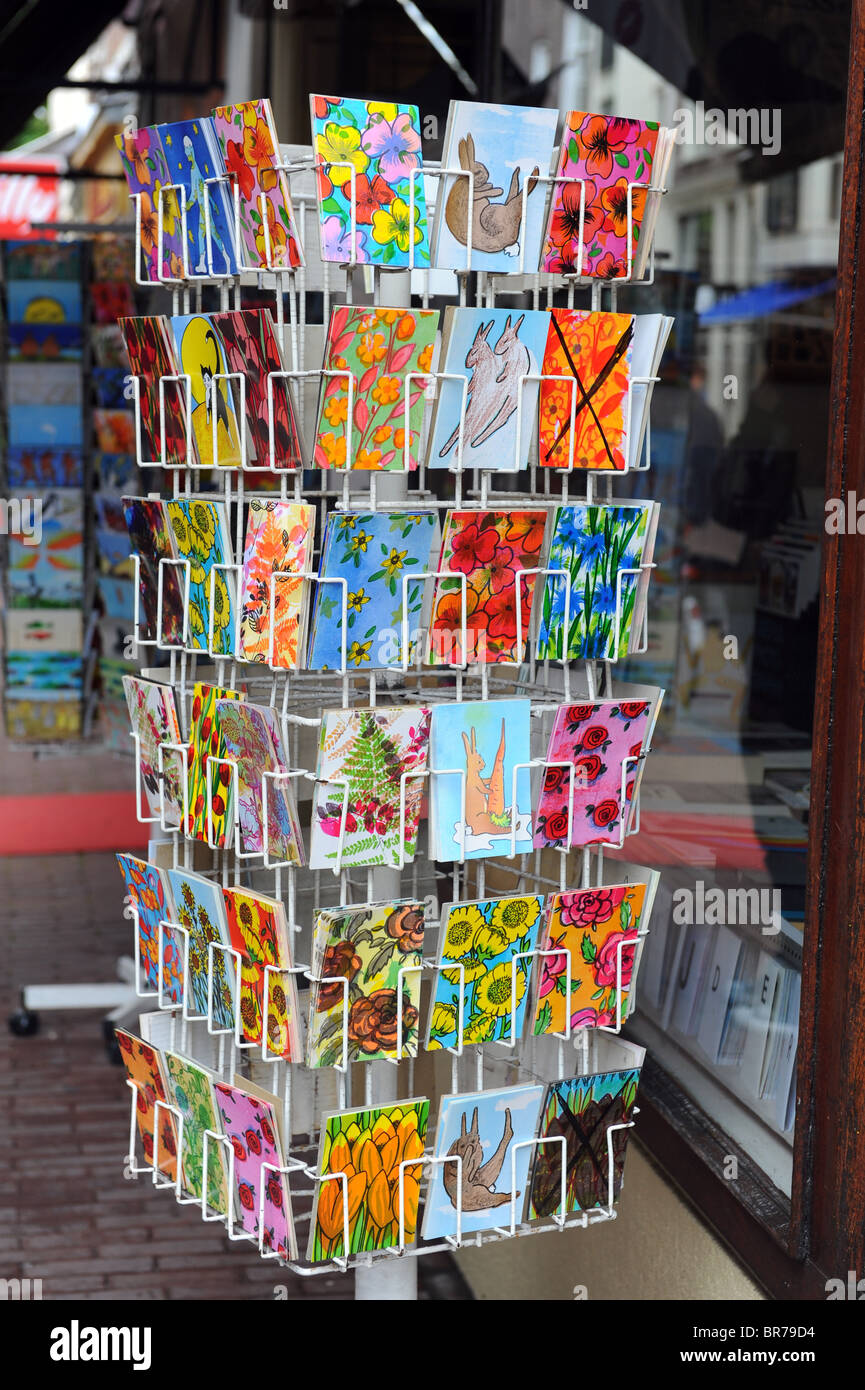 Colourful postcards on sale in a rack outside a shop - Stock Image