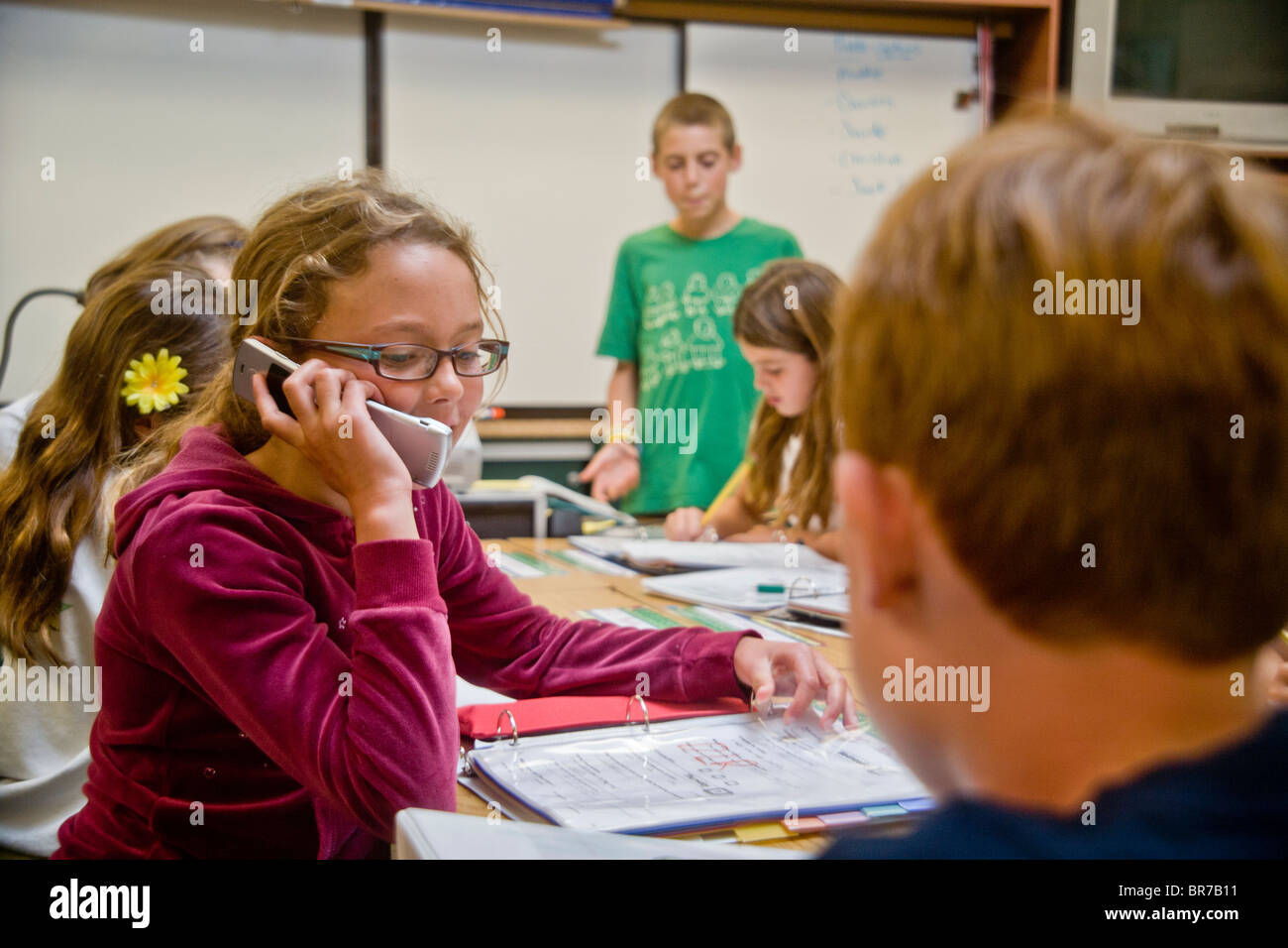 A middle school student uses a cell phone in class in San Clemente, CA. - Stock Image