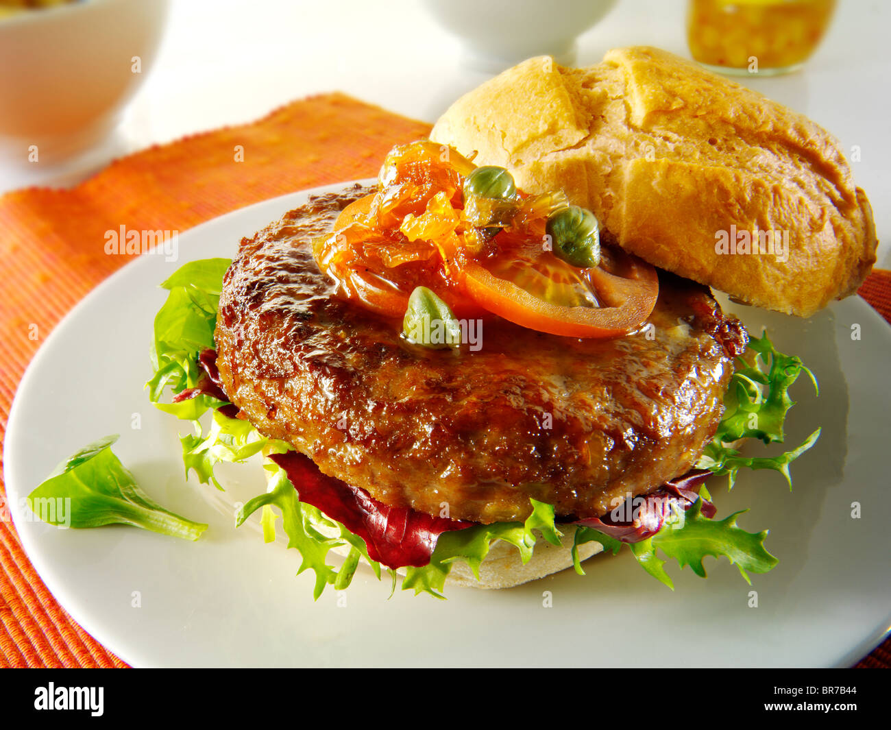 Beef burgers in a bread bun with salad & garnish - Stock Image