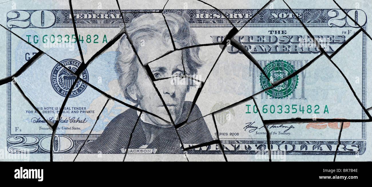 Cracked American twenty dollar bill concept to represent an economic crisis - Stock Image