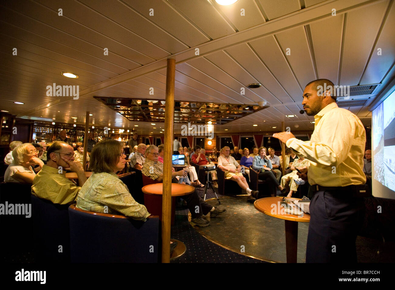 Lobo Merchane lead naturalist for the cruise ship Santa Cruz gives a slide presentation to tour members about their - Stock Image