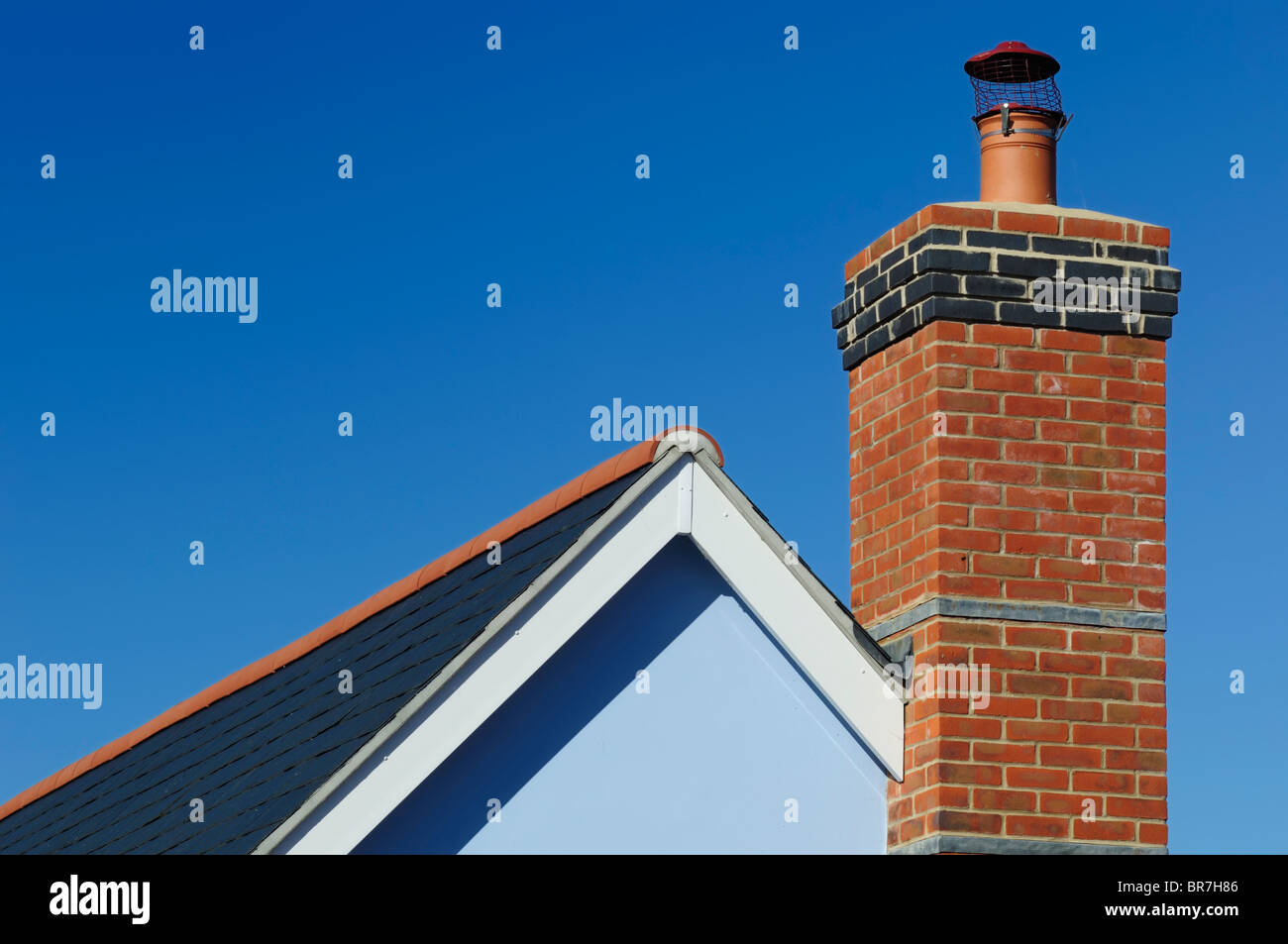 A close up view of a brick chimney on a house, beneath a clear blue sky. - Stock Image