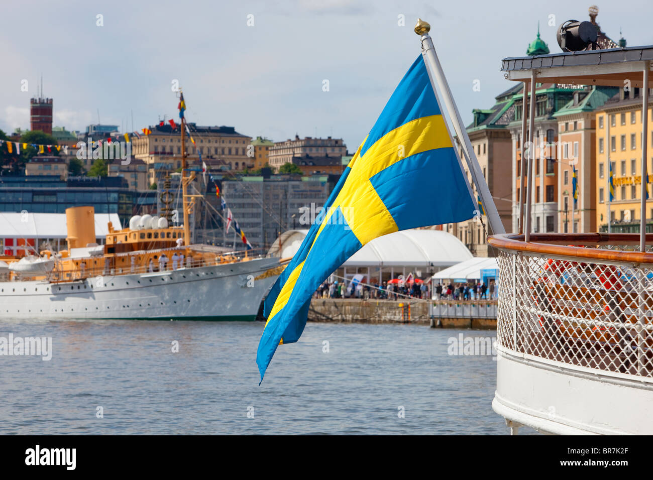 Sweden Stockholm - Swedish flag on one of the many boats anchored at The Old Town - Gamla Stan - Stock Image