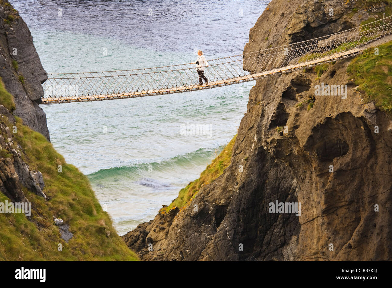 Young woman crossing the Carrick-a-Rede rope bridge near the village of Ballintoy on the County Antrim coast, Northern - Stock Image