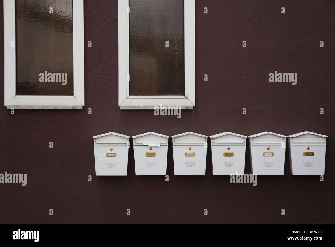 A row of postboxes letter boxes underneath a pair of windows in Olot Catalonia Spain - Stock Image